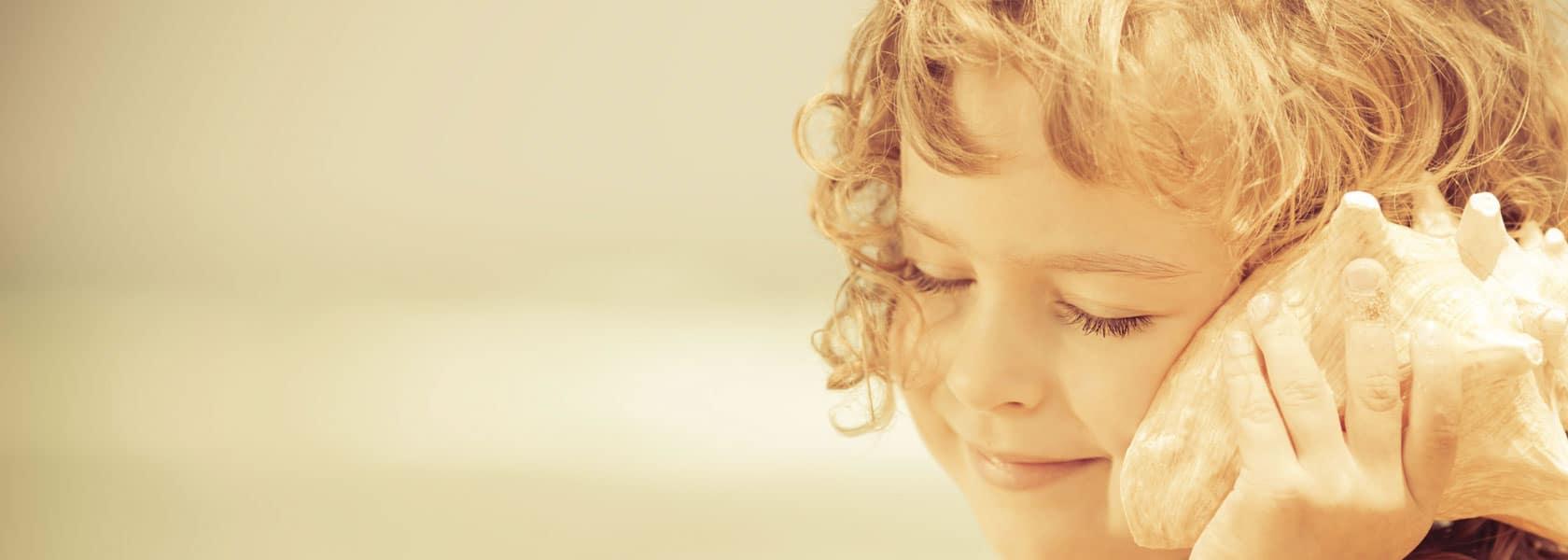 Bambina che ascolta il mare in una conchiglia