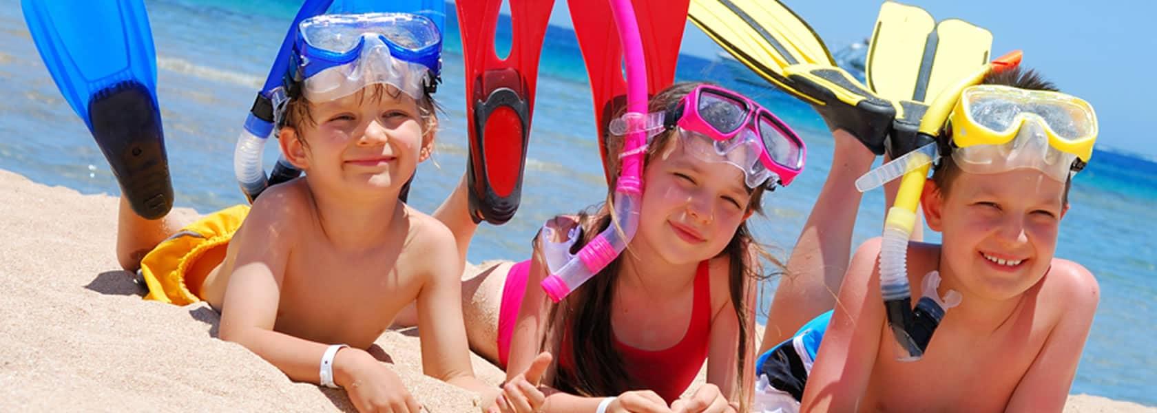 Bambini felici con maschera da sub e pinne che ridono felici in una spiaggia